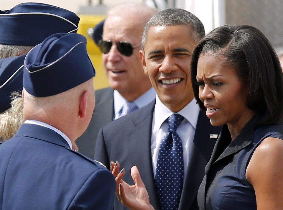 Photo -   First lady Michelle Obama, accompanied by President Barack Obama and Vice President Joe Biden, talks with service members upon their arrival at Pease Air National Guard Base in Portsmouth, N.H., Friday, Sept. 7, 2012. (AP Photo/Winslow Townson)