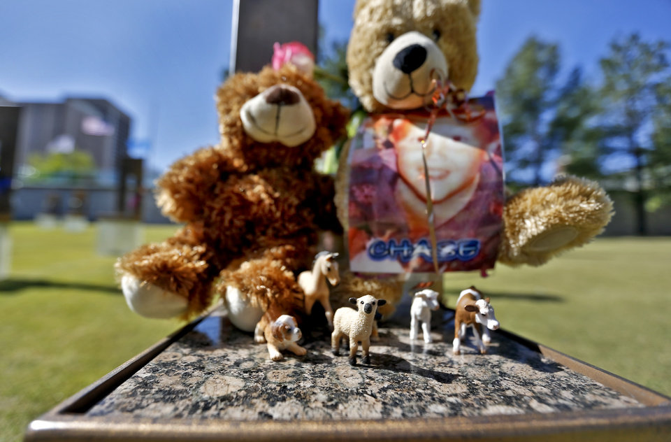 Photo - Toy animals sit on the chair of bombing victim Chase Dalton Smith during the 18th Anniversary Remembrance Ceremony of the Oklahoma City bombing on Friday, April 19, 2013, in Oklahoma City, Okla.   Photo by Chris Landsberger, The Oklahoman