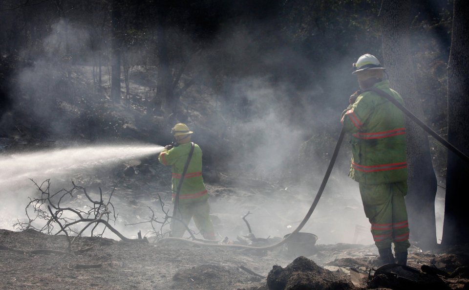 Photo - Two Tuttle firefighters assist in controlling hot spots on land behind a home near NE 66 and Sooner that burned in Tuesday's fire when wildfires ravaged land and property that stretched from NE 50 on the south to Hefner Road on the north.  The fire extended from Sooner Road to Midwest Boulevard.    Photo taken Wednesday, Aug. 31, 2011. Photo by Jim Beckel, The Oklahoman