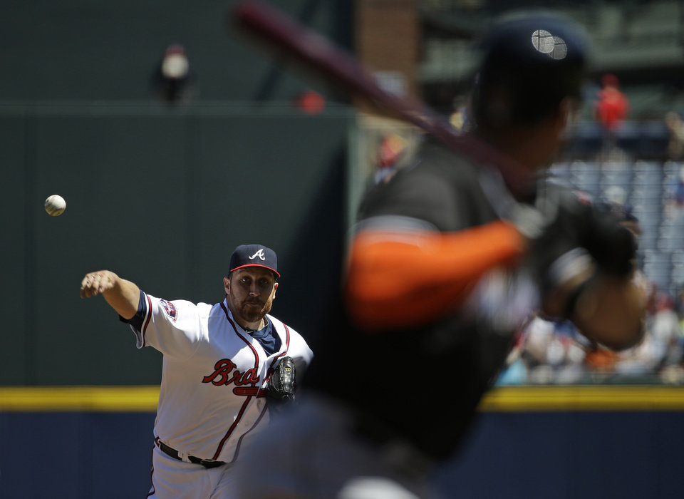 Photo - Atlanta Braves starting pitcher Aaron Harang, left, throws to Miami Marlins' Giancarlo Stanton in the first inning of a baseball game, Wednesday, April 23, 2014, in Atlanta. (AP Photo/David Goldman)
