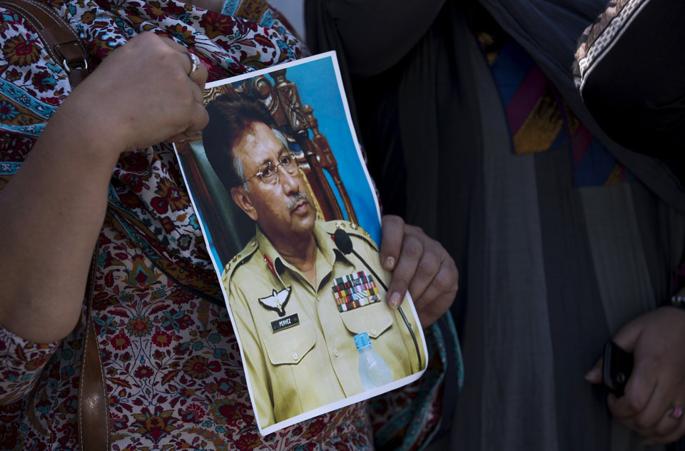 Photo - A supporter of former Pakistani President Pervez Musharraf holds a photo of him outside the special court in Islamabad, Pakistan, Monday, March 31, 2014. A special Pakistani court Monday indicted former military ruler Musharraf on five counts of high treason, marking a sharp blow to the country's powerful military. (AP Photo/B.K. Bangash)