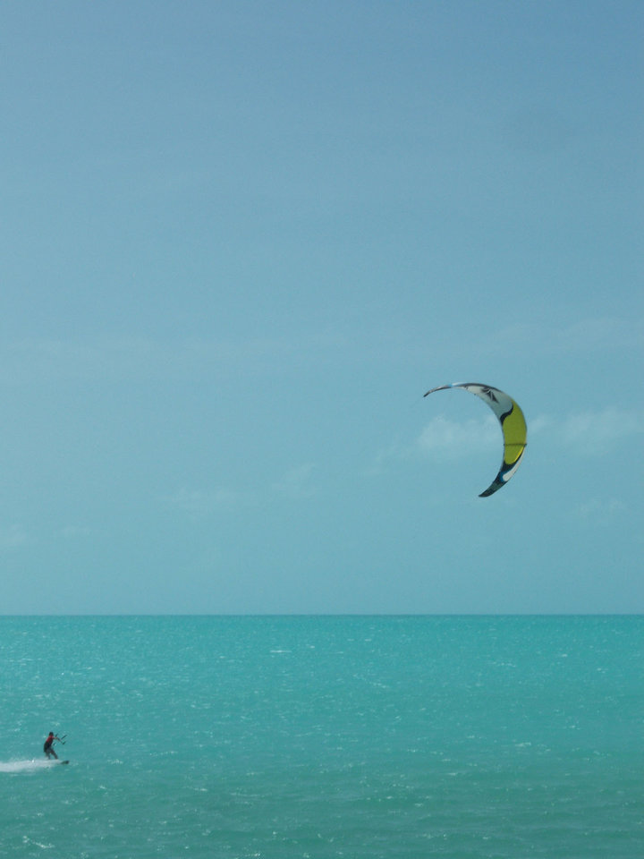 Photo -  A kite-boarder enjoys the blue waters of Long Beach Bay in the islands of Turks and Caicos. Photo courtesy of Adriana Gardella.