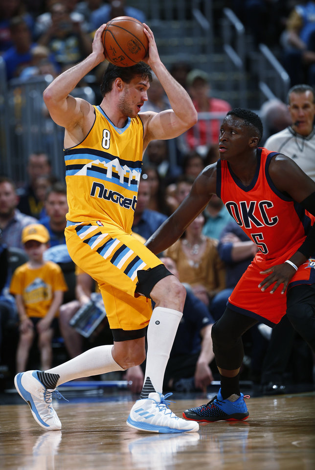 Photo - Denver Nuggets forward Danilo Gallinari (8) goes up against Oklahoma City Thunder guard Victor Oladipo (5) during the first half of a basketball game, Sunday, April 9, 2017, in Denver. (AP Photo/Jack Dempsey)