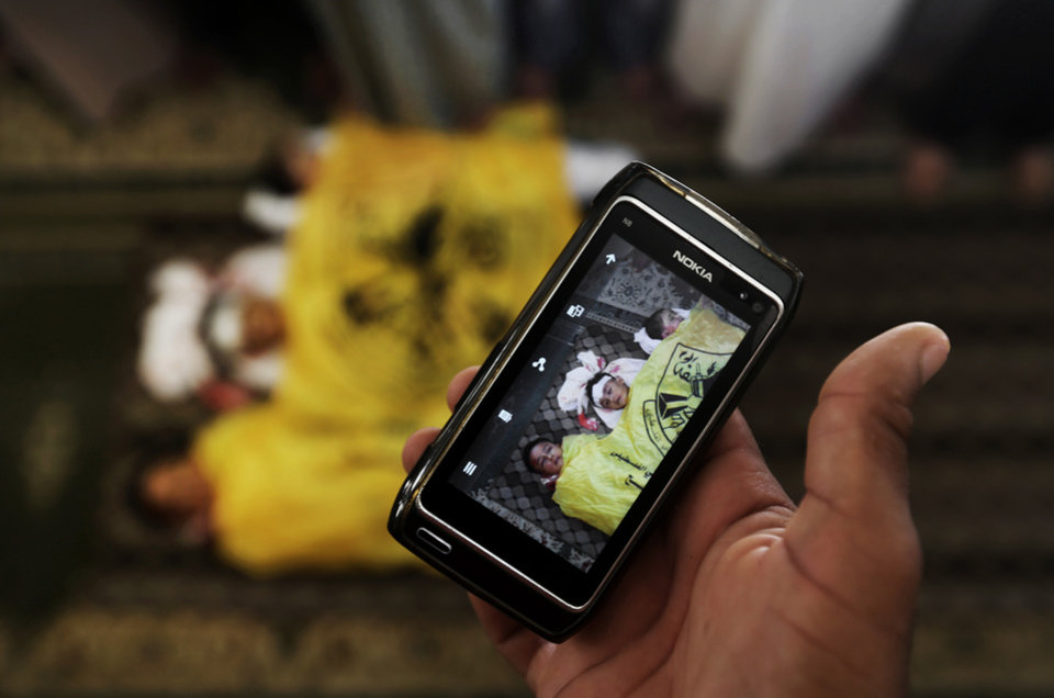 Photo - A man takes a photo with his mobile phone of the lifeless bodies of Qasim Alwan, 4, Imad Alwan, 6, and Rizk Hayek, 1, who were killed Friday by an Israeli tank shell, during their funeral in Gaza City, Saturday, July 19, 2014. Relatives say the tank shell kit the Alwan family's kitchen, killing Qasim and Imad. Hayek, who lived nearby, was killed by shrapnel. (AP Photo/Hatem Moussa)