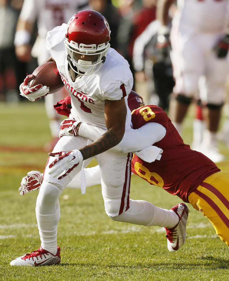 Photo - Oklahoma's K.J. Young (1) is tackled by Iowa State's Kenneth Lynn (8) after a catch in the first quarter during a college football game between the University of Oklahoma Sooners (OU) and the Iowa State Cyclones (ISU) at Jack Trice Stadium in Ames, Iowa, Saturday, Nov. 1, 2014. Photo by Nate Billings, The Oklahoman