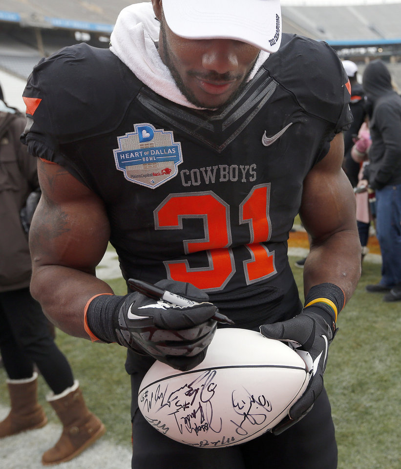 Photo - Oklahoma State's Jeremy Smith (31) signs a football for a fan during the Heart of Dallas Bowl football game between the Oklahoma State University (OSU) and Purdue University at the Cotton Bowl in Dallas,  Tuesday,Jan. 1, 2013. Photo by Sarah Phipps, The Oklahoman