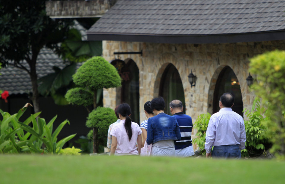 Photo - Chinese relatives of passengers aboard a missing Malaysia Airlines plane, walk back to their rooms at a resort in Cyberjaya, Malaysia, Thursday, March 20, 2014. Flight 370 disappeared March 8 on a night flight from Kuala Lumpur to Beijing. Malaysian authorities have not ruled out any possible explanation, but have said the evidence so far suggests the flight was deliberately turned back across Malaysia to the Strait of Malacca, with its communications systems disabled. (AP Photo/Lai Seng Sin)