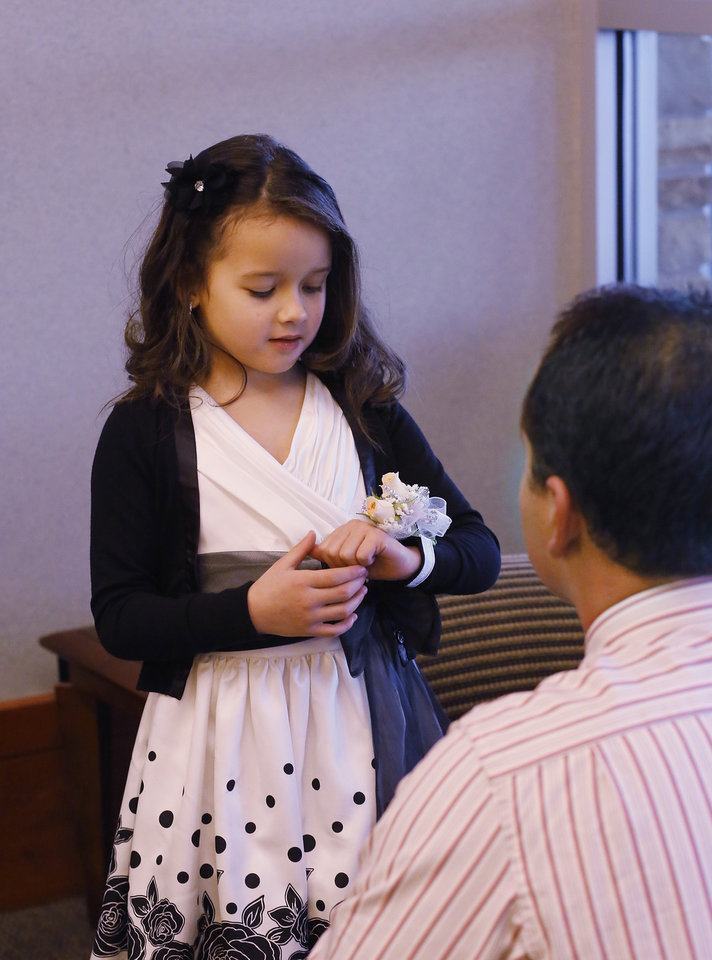 A girl admires her corsage after her dad placed it on her wrist. Midwest City Parks and Recreation Department hosted the city\'s annual Daddy-Daughter Dance that featured three 90-minute dance sessions at the Reed Center on Saturday, Feb. 16, 2013. Photo by Jim Beckel, The Oklahoman