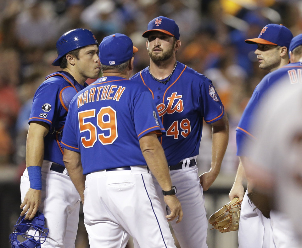 Photo - New York Mets pitching coach Dan Warthen (59) talks to Jonathon Niese (49) as David Wright, right, and Travis d'Arnaud, left, listen during the seventh inning of a baseball game against the San Francisco Giants Friday, Aug. 1, 2014, in New York. (AP Photo/Frank Franklin II)