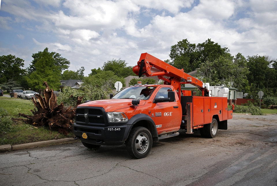 Photo - An OG and E truck drives in a neighborhood near 21st and McKinley after an apparent tornado moved through the area in Oklahoma City, Sunday, May 26, 2019.  [Sarah Phipps/The Oklahoman]