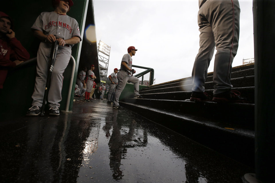 Photo - Cincinnati Reds' Chris Heisey, center, stands on the steps as he prepares to bat in the rain during the sixth inning of a baseball game against the Washington Nationals at Nationals Park on Wednesday, May 21, 2014, in Washington. (AP Photo/Alex Brandon)