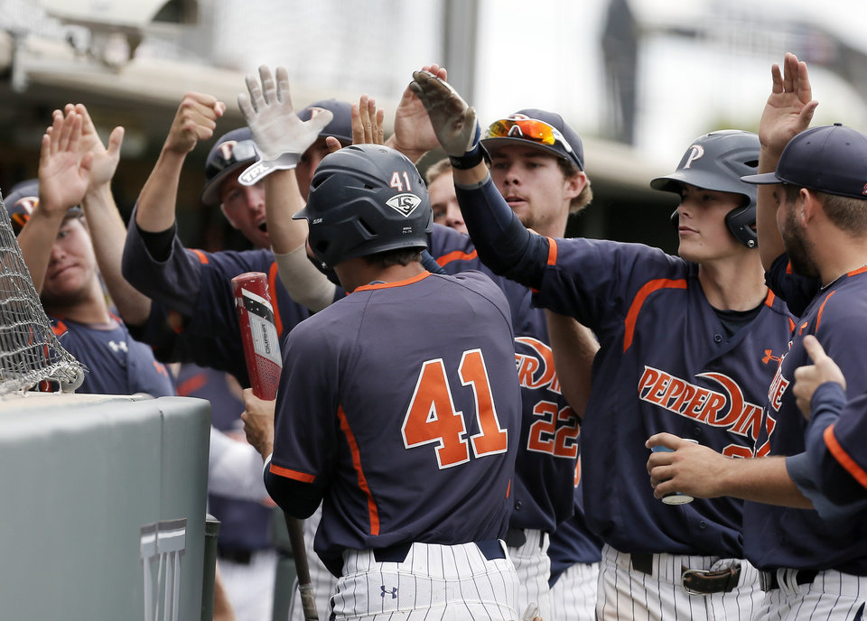 Photo - Pepperdine's Brandon Caruso (41) is congratulated by teammates after scoring a run on an RBI by teammate Aaron Brown, not pictured, during the first inning of an NCAA college baseball tournament super regional game against the TCU in Fort Worth, Texas, Monday, June 9, 2014. (AP Photo/Brandon Wade)