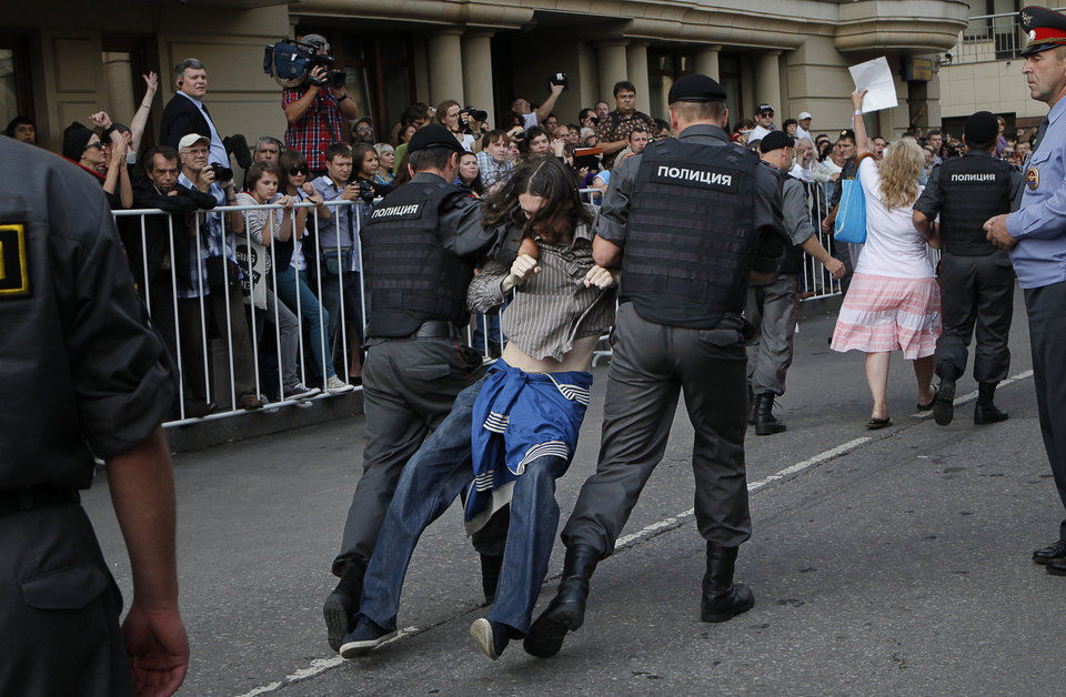 Photo -   Police officers detain supporters of the Russian punk group Pussy Riot outside a court in Moscow, Russia, Friday, Aug. 17, 2012. A Moscow judge sentenced three members of the provocative punk band Pussy Riot to two years in prison each on hooliganism charges on Friday following a trial that has drawn international outrage as an emblem of Russia's intolerance of dissent. (AP Photo/Alexander Zemlianichenko)