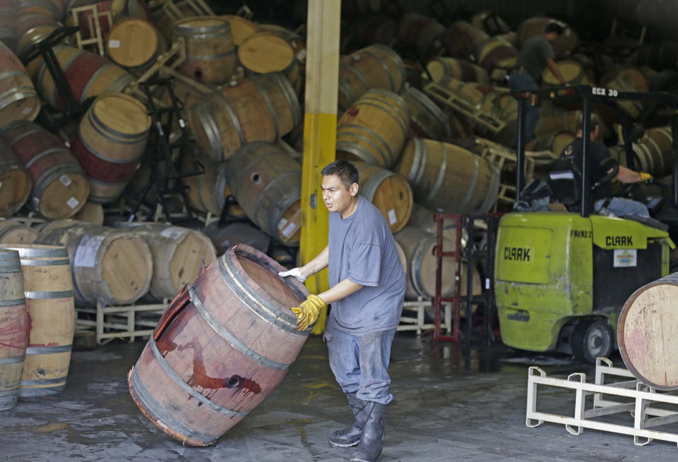 Photo - A worker removes an earthquake-damaged wine barrel from a barrel storage facility Monday, Aug. 25, 2014, in Napa, Calif. A powerful earthquake that struck the heart of California's wine country caught many people sound asleep, sending dressers, mirrors and pictures crashing down around them and toppling wine bottles in vineyards around the region. The magnitude-6.0 quake struck at 3:20 a.m. PDT Sunday near the city of Napa. (AP Photo/Eric Risberg)
