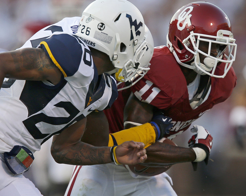 Photo - Oklahoma's Lacoltan Bester (11) loses the ball as he is hit during a college football game between the University of Oklahoma Sooners (OU) and the West Virginia University Mountaineers at Gaylord Family-Oklahoma Memorial Stadium in Norman, Okla., on Saturday, Sept. 7, 2013. Photo by Bryan Terry, The Oklahoman
