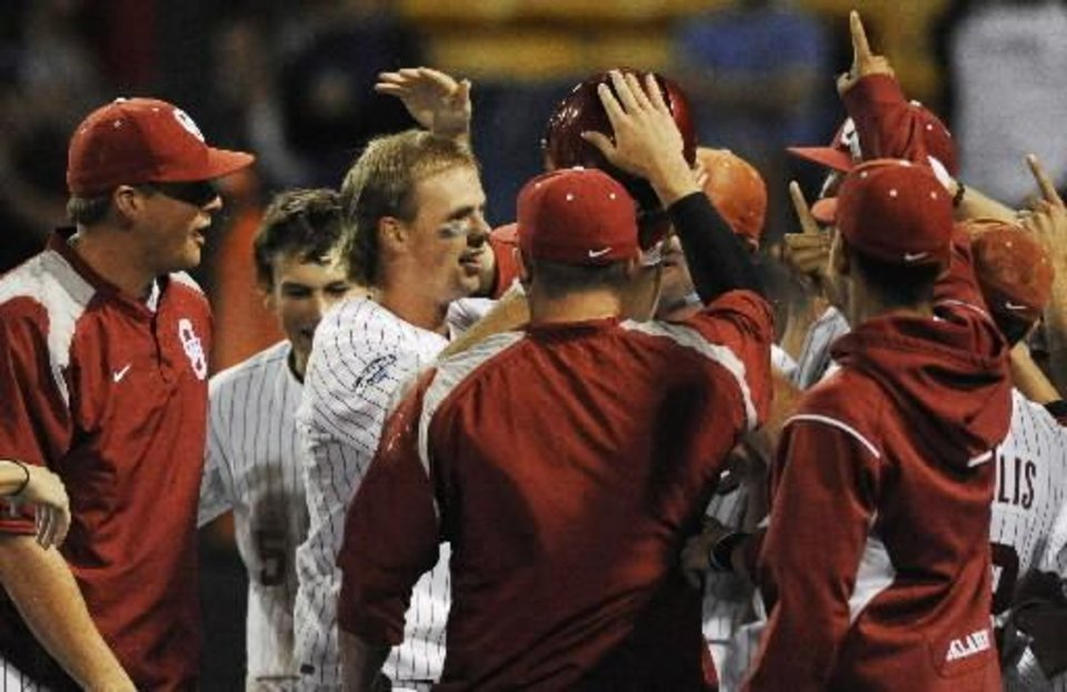 Oklahoma players celebrate with Garrett Buechele, center left, after he hit a solo home run against South Carolina in the eighth inning of an NCAA College World Series baseball game in Omaha, Neb., Sunday, June 20, 2010. (AP Photo/Eric Francis)