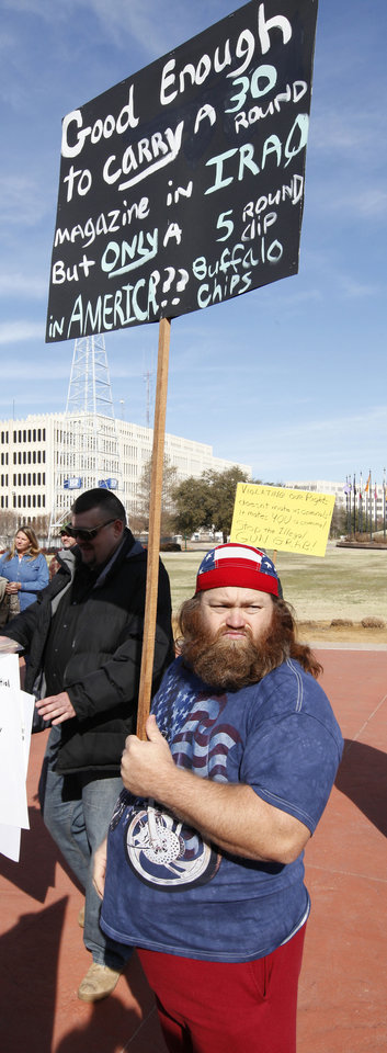 Chris French, Rush Springs, carries a protest sign as members of the Oklahoma Defense Force hold a rally on the north side of the state Capitol in Oklahoma City on Friday.  Photo by Paul B. Southerland, The Oklahoman <strong>PAUL B. SOUTHERLAND - PAUL B. SOUTHERLAND</strong>