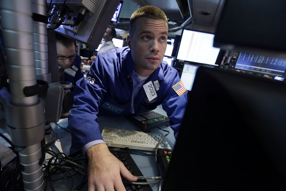 Photo - Specialist Frank Masiello works at his post on the floor of the New York Stock Exchange Friday, Aug. 16, 2013. Stocks bounced back Friday from consecutive days of significant declines, with more evidence of a rebounding U.S. housing market. (AP Photo/Richard Drew)