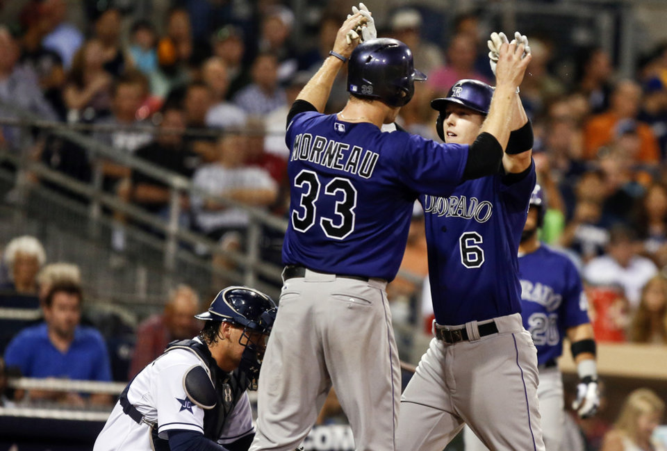 Photo - Colorado Rockies' Corey Dickerson is greeted by Justin Morneau, left, after blasting a three-run home run against the San Diego Padres in the sixth inning of a baseball game Monday, Aug. 11, 2014, in San Diego. (AP Photo/Lenny Ignelzi)
