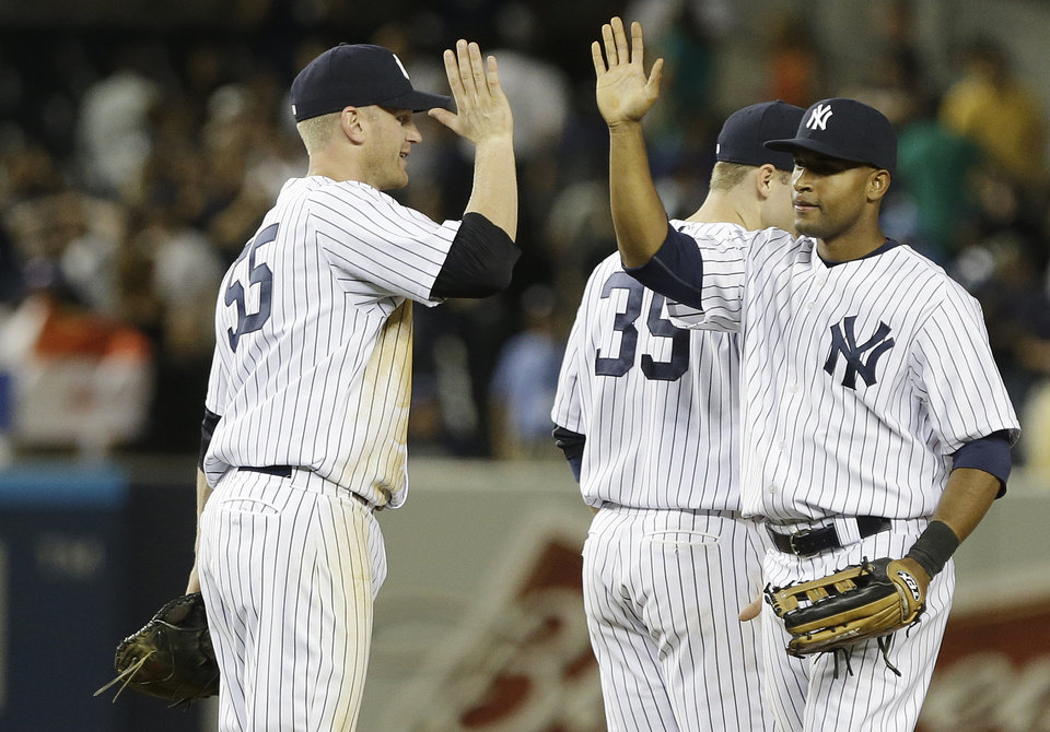 New York Yankees' Zoilo Almonte, right, celebrates with teammate Lyle Overbay (55) after a baseball game against the Tampa Bay Rays, Friday, June 21, 2013, in New York. The Yankees won the game 6-2. (AP Photo/Frank Franklin II)
