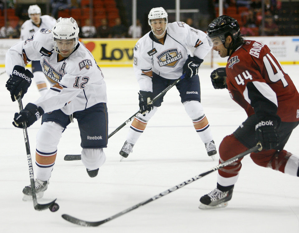 Photo - Alexandre Giroux of the Oklahoma City Barons gets past Travis Gawryletz of the Lake Erie Monsters during an AHL hockey game at the Cox Convention Center in Oklahoma City, Tuesday, October 19, 2010.  Photo by Bryan Terry, The Oklahoman