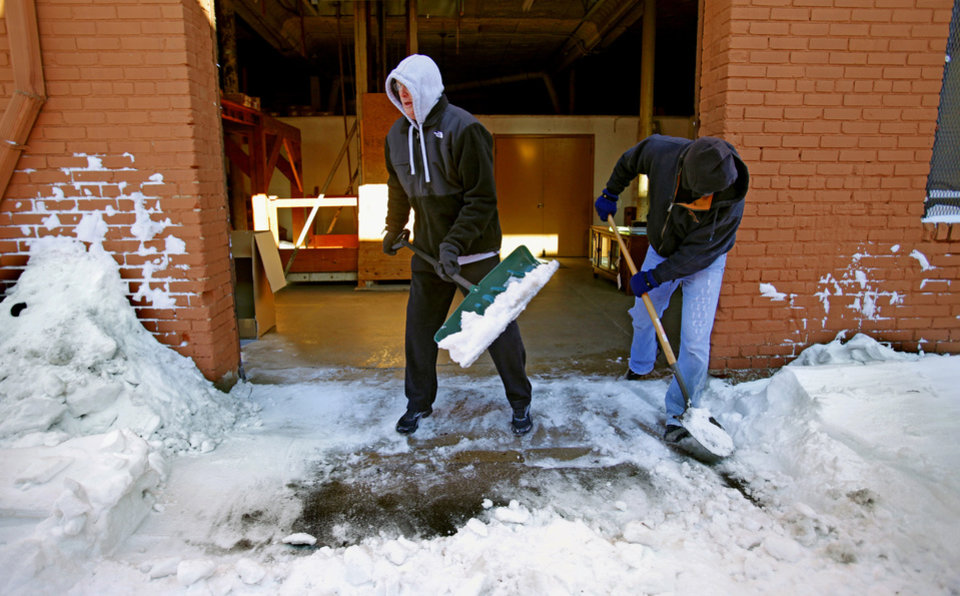 Photo - Scott Blair, owner Blair Home Furnishings, and Danny Jennings clear snow from the alley behind the store on Wednesday, February 2, 2011, in Norman, Okla.  Photo by Steve Sisney, The Oklahoman