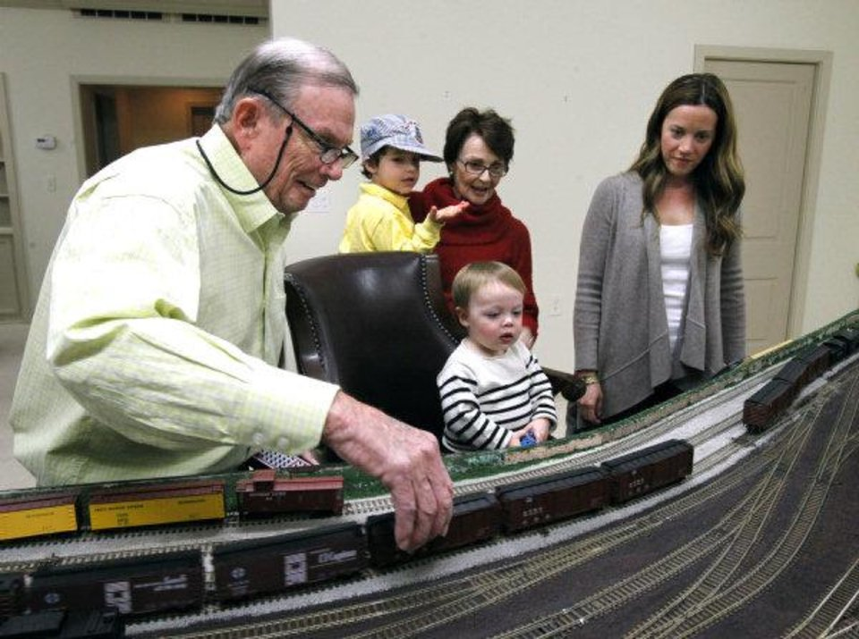 Photo - Jimmy Samis demonstrates his train collection to his great-grandchildren Sam Kirkpatrick, 3, and 16-month-old Thomas Fellers, his daughter Linda James, and grandaughter Carter Fellers, at his home in Nichols Hills on Oct. 28. Photo by Paul Hellstern, The Oklahoman  PAUL HELLSTERN