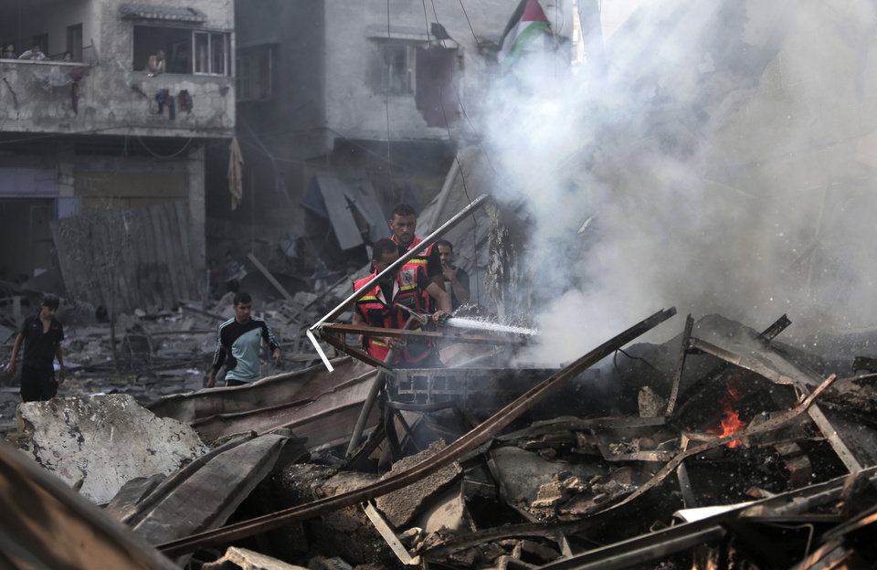 Photo - Palestinian firefighters extinguish a fire in the rubble of the destroyed 15-story Basha Tower that was leveled in early morning Israeli airstrikes in Gaza City, Tuesday, Aug. 26, 2014. Israel bombed two Gaza City high-rises with dozens of homes and shops Tuesday, collapsing the 15-story Basha Tower and severely damaging the Italian Complex in a further escalation in seven weeks of cross-border fighting with Hamas. Both buildings were evacuated after receiving warnings of impending strikes. (AP Photo/Khalil Hamra)