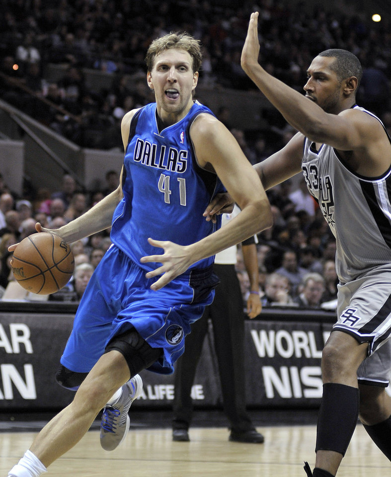 Dallas Mavericks' Dirk Nowitzki, left, of Germany, drives around San Antonio Spurs' Boris Diaw, of France, during the second half of an NBA basketball game, Sunday, Dec. 23, 2012, in San Antonio. San Antonio won 129-91. (AP Photo/Darren Abate)