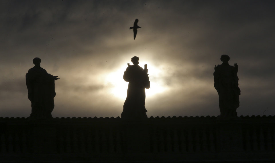 Photo - A seagull flies over statues at St. Peter's Basilica at the Vatican, Monday, Feb. 25, 2013. Pope Benedict XVI has changed the rules of the conclave that will elect his successor, allowing cardinals to move up the start date if all of them arrive in Rome before the usual 15-day transition between pontificates. Benedict signed a legal document, issued Monday, with some line-by-line changes to the 1996 Vatican law governing the election of a new pope. It is one of his last acts as pope before resigning Thursday. (AP Photo/Dmitry Lovetsky)