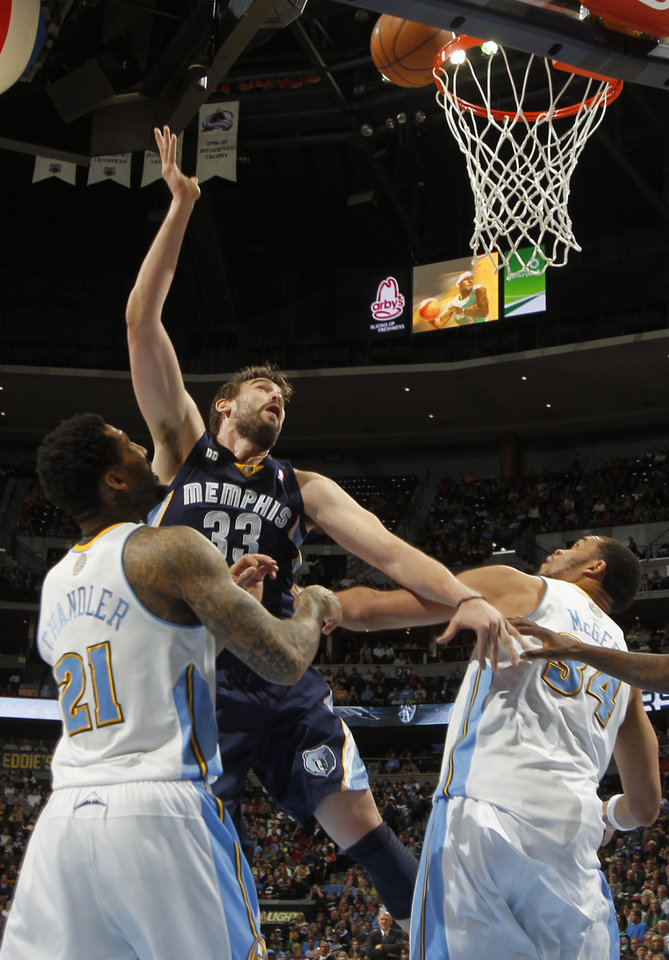Photo - Memphis Grizzlies center Marc Gasol, center, of Spain, shoots between Denver Nuggets forwards Wilson Chandler, left, and JaVale McGee in the first quarter of an NBA basketball game in Denver, Friday, March 15, 2013. (AP Photo/David Zalubowski)