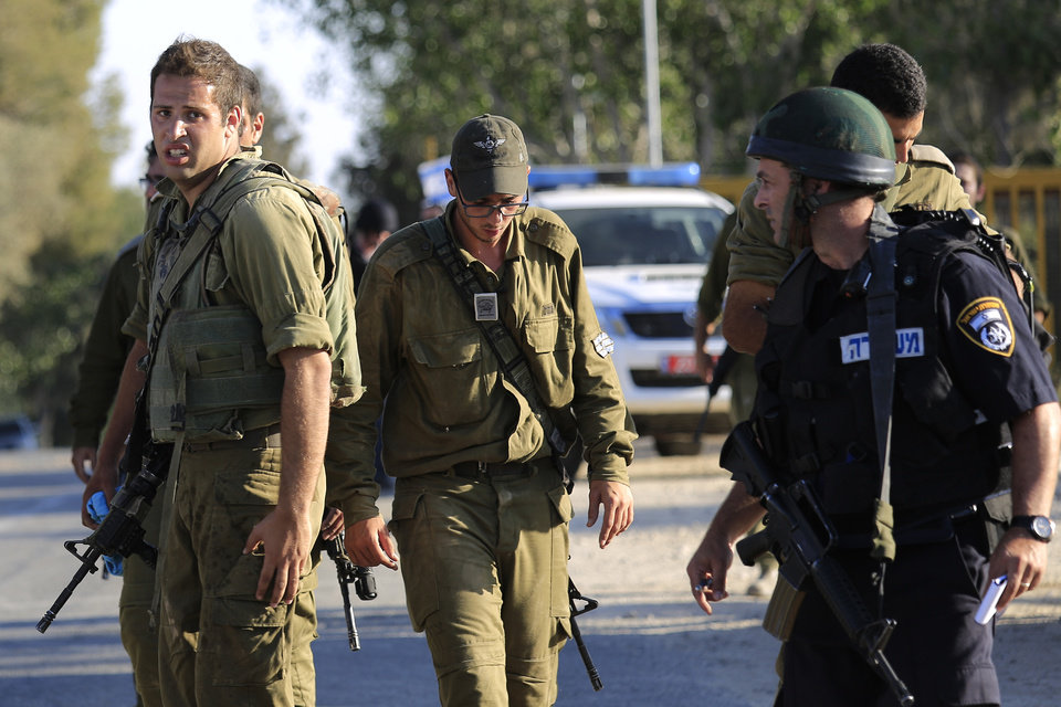 Photo - Israeli solders and police at the site near the Israeli Gaza border, were a man was injured from a mortar shell fired from the Gaza Strip, Sunday, Aug. 3, 2014. (AP Photo/Tsafrir Abayov)