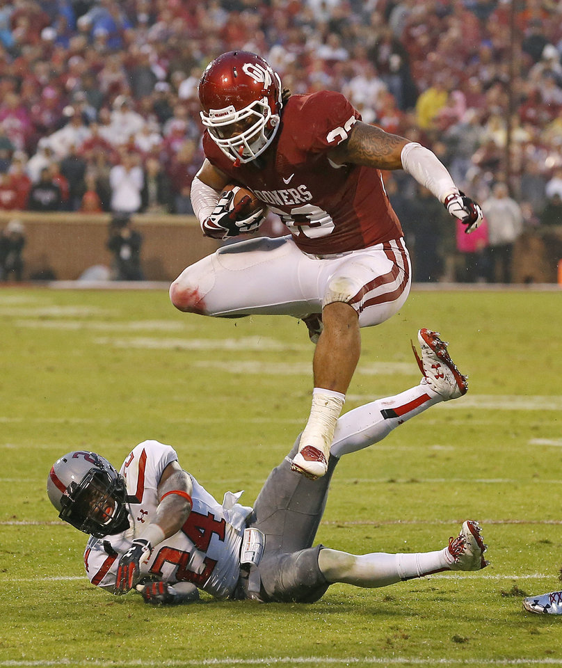 Oklahoma's Trey Millard (33) leaps over Texas Tech's Bruce Jones (24) during a college football game between the University of Oklahoma Sooners (OU) and the Texas Tech Red Raiders at Gaylord Family-Oklahoma Memorial Stadium in Norman, Okla., on Saturday, Oct. 26, 2013. Oklahoma won 38-30. Photo by Bryan Terry, The Oklahoman