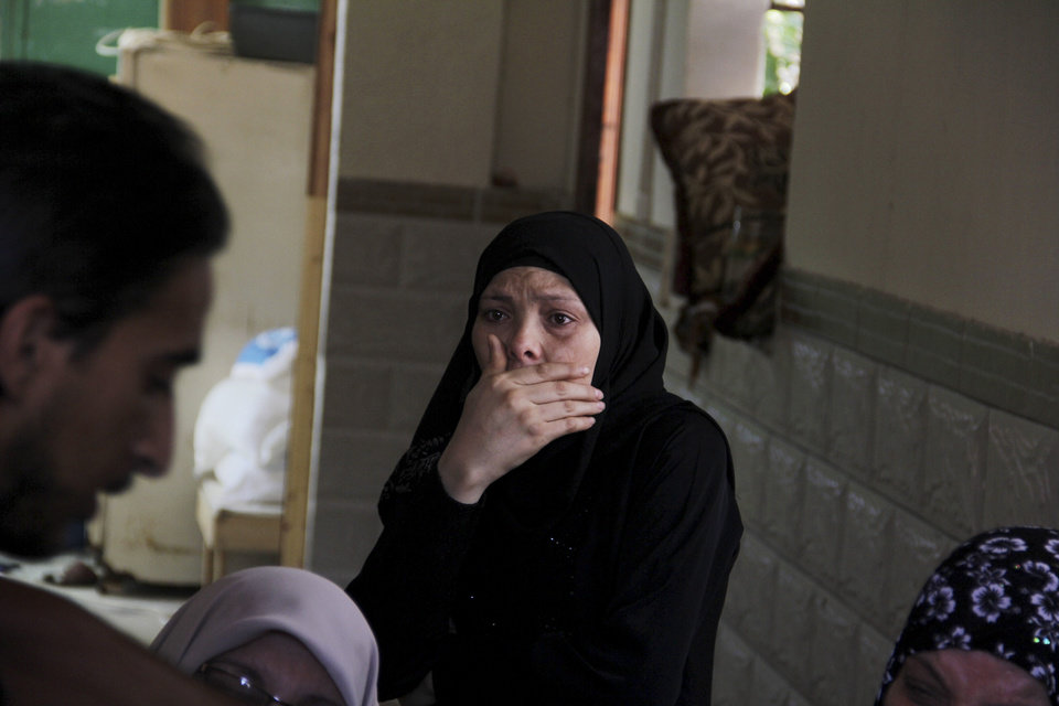 Photo - Palestinian relatives cry during the funeral of a senior commander of the Hamas military wing, Mohammed Abu Shamaleh, who was killed in early morning Israeli strikes, at his family house in the Rafah refugee camp in the southern Gaza Strip, Thursday, Aug. 21, 2014. The pre-dawn strike leveled a four-story house in a densely populated neighborhood of Rafah, killing at least six people, including Abu Shamaleh and two other senior Hamas commanders. (AP Photo/Hatem Ali)