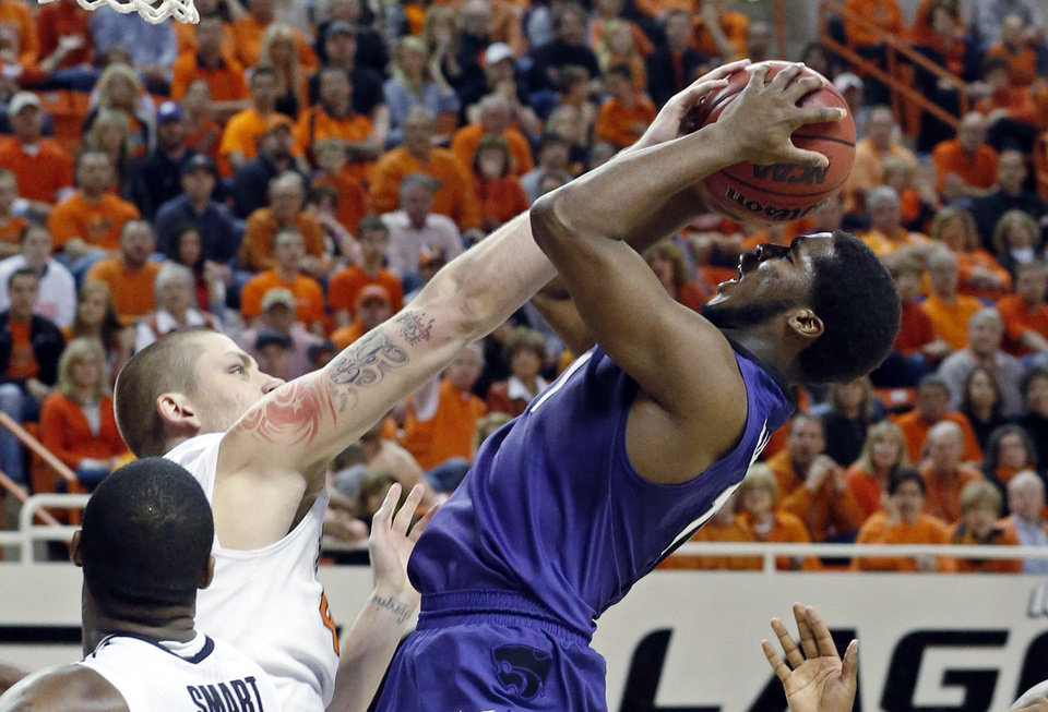 Photo - Oklahoma State forward Philip Jurick, left, fouls Kansas State forward Nino Williams as he shoots in the second half of an NCAA college basketball game in Stillwater, Okla., Saturday, March 9, 2013. Oklahoma State won 76-70. (AP Photo/Sue Ogrocki)