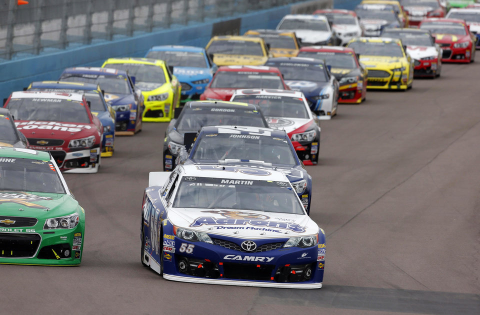 Mark Martin leads the pack at the start of the NASCAR Sprint Cup Series auto race, Sunday, March 3, 2013, in Avondale, Ariz. (AP Photo/Matt York)