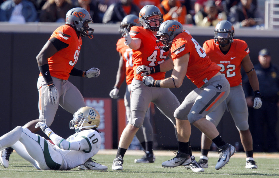 Photo - Oklahoma State's Cooper Bassett (80) and Caleb Lavey (45) celebrate a sack on Baylor's Robert Griffin III (10) during a college football game between the Oklahoma State University Cowboys (OSU) and the Baylor University Bears (BU) at Boone Pickens Stadium in Stillwater, Okla., Saturday, Oct. 29, 2011. Photo by Sarah Phipps, The Oklahoman