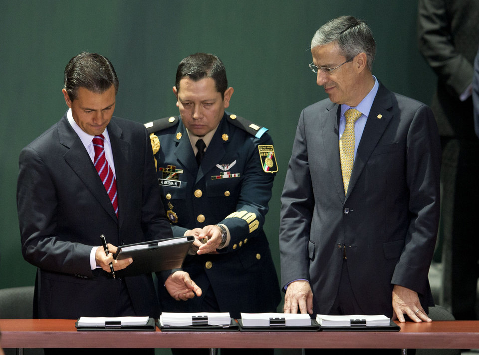 Photo - Mexican President Enrique Pena Nieto, left, is accompanied by House Speaker Jose Gonzalez Morfin, right, as he signs into law a historic energy reform bill at the National Palace in Mexico City, Monday, Aug. 11, 2014. The law will open the state-run oil, gas and electricity industries to foreign and private companies. Mexico is hoping for tens of billions of dollars in outside investment in deep-water oil drilling and shale gas production.(AP Photo/Rebecca Blackwell)