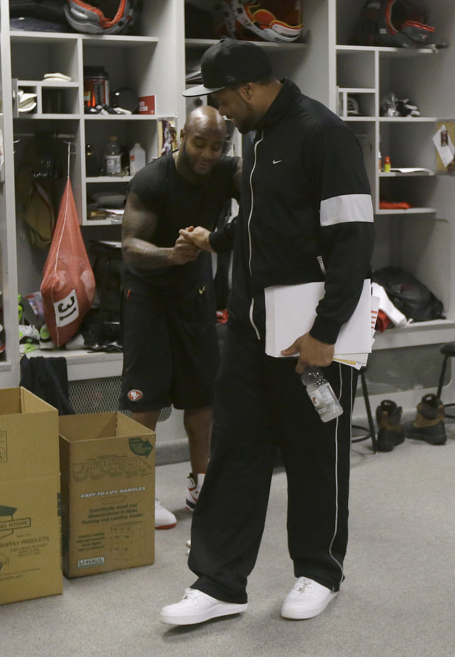 Photo - San Francisco 49ers linebacker Ahmad Brooks, foreground, shakes hands with safety Donte Whitner in the locker room at an NFL training facility in Santa Clara, Calif., Monday, Jan. 20, 2014. The 49ers lost to the Seattle Seahawks in the NFC Championship Game. (AP Photo/Jeff Chiu)