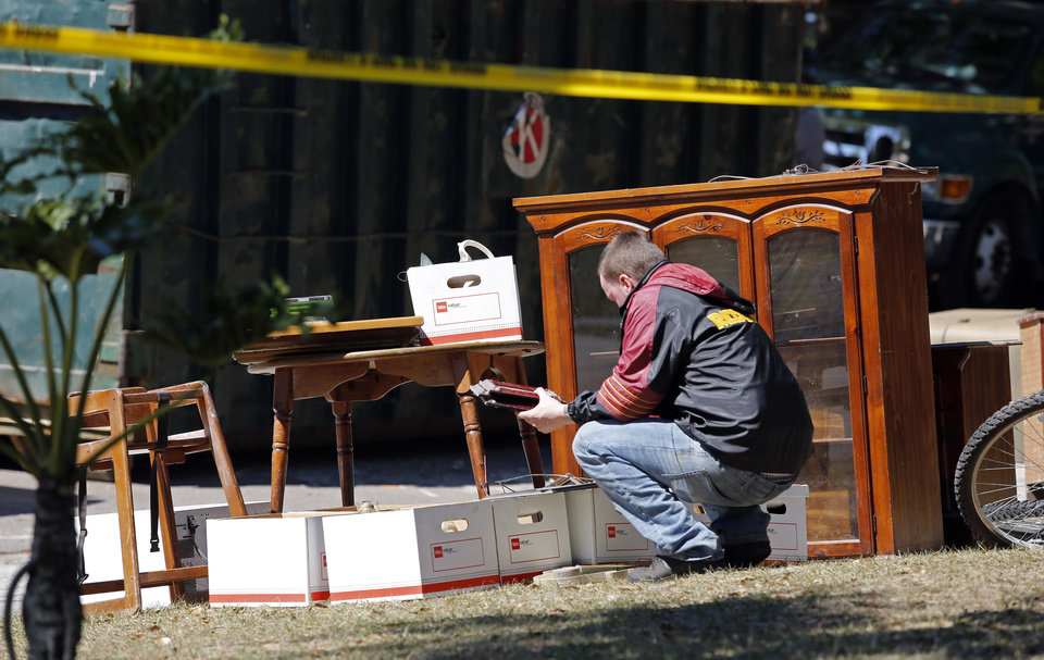 Photo - Family members search through items that were recovered from the home of Jeff Bush, Monday, March 4, 2013 in Seffner, Fla.  A sinkhole opened up underneath the house late Thursday, Feb. 28, 2013, swallowing Jeff Bush, 37.  The 20-foot-wide opening of the sinkhole was almost covered by the house, and rescuers said there were no signs of life since the hole opened Thursday night.  (AP Photo/Scott Iskowitz)