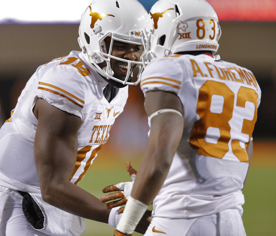 Photo - Texas' Tyrone Swoopes (18) celebrates with Armanti Foreman (83) after a touchdown during the college football game between the Oklahoma State University Cowboys (OSU) the University of Texas Longhorns (UT) at Boone Pickens Staduim in Stillwater, Okla. on Saturday, Nov. 15, 2014.  Photo by Chris Landsberger, The Oklahoman