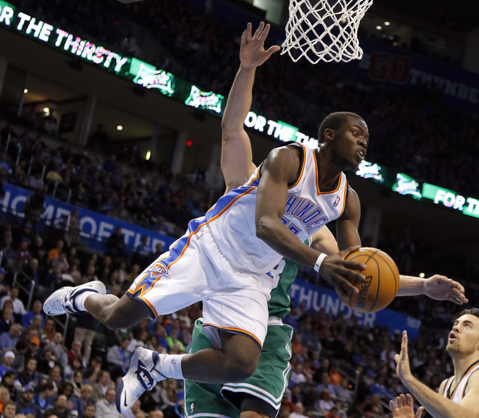 Photo - Oklahoma City's Reggie Jackson (15) flies through the air after colliding with Boston's Kris Humphries (43) during the NBA game between the Oklahoma City Thunder and the Boston Celtics at the Chesapeake Energy Arena., Sunday, Jan. 5, 2014. Photo by Sarah Phipps, The Oklahoman