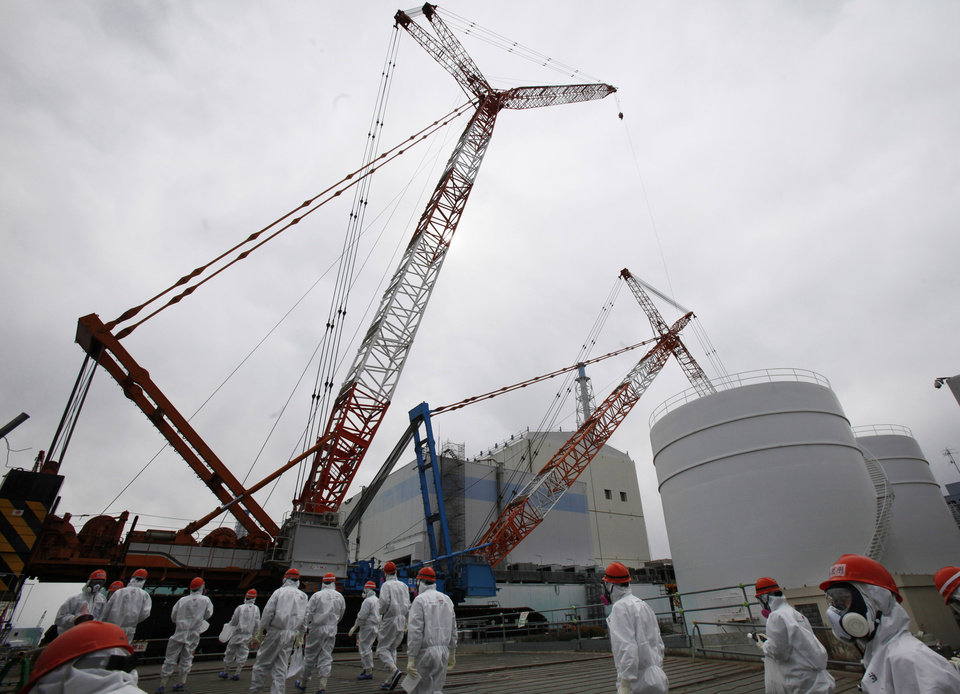 Photo - Tokyo Electric Power Co. (TEPCO) staff and journalists walk in front of the No. 1 reactor at the Fukushima Dai-ichi nuclear power plant during a press tour in Okuma town, Fukushima prefecture, northeastern Japan, Monday, March 10, 2014. The radioactive water that has accumulated at the crippled nuclear power plant remains the biggest problem hampering the cleanup process three years after the disaster. (AP Photo/Koji Sasahara, Pool)