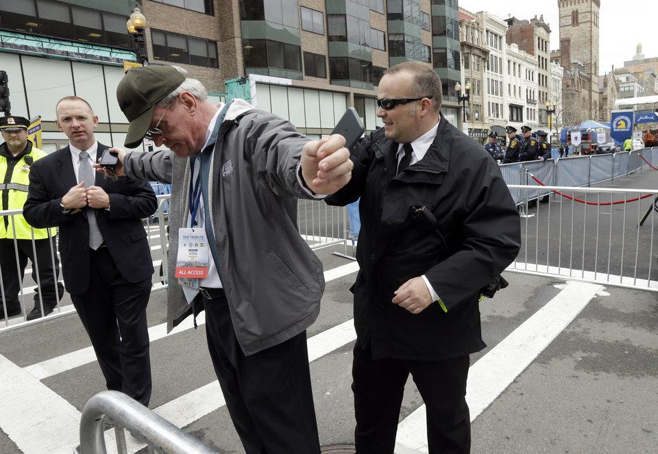 Photo - A law enforcement official searches a man near the finish line of the Boston Marathon, Tuesday, April 15, 2014, in Boston. Vice President Joe Biden is expected to be among the dignitaries Tuesday during ceremonies to honor the victims, first responders, doctors and nurses who helped them, after the Boston Marathon bombings, at the Hynes Convention Center in Boston. (AP Photo/Steven Senne)