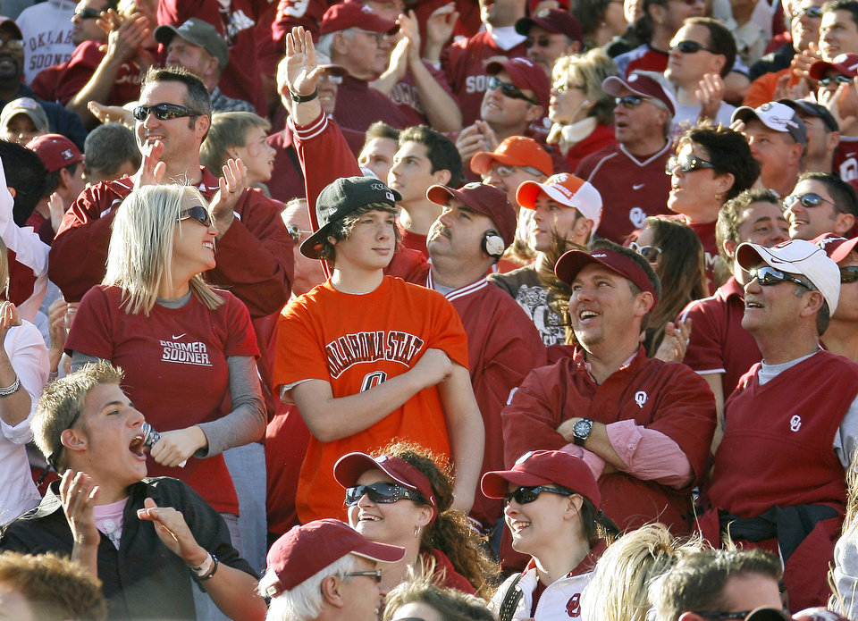 Photo - OU fans celebrate as an OSU watches during the second half of the Bedlam college football game between the University of Oklahoma Sooners (OU) and the Oklahoma State University Cowboys (OSU) at the Gaylord Family-Oklahoma Memorial Stadium on Saturday, Nov. 28, 2009, in Norman, Okla.