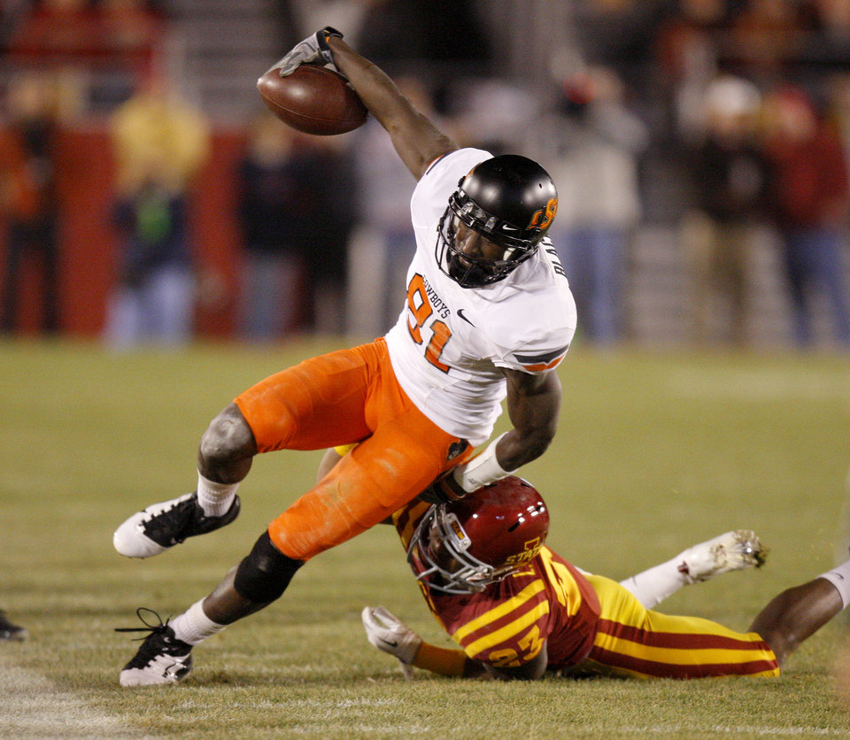 Photo - Oklahoma State's' Justin Blackmon (81) is brought down by Iowa State's Leonard Johnson (23) during a college football game between the Oklahoma State University Cowboys (OSU) and the Iowa State University Cyclones (ISU) at Jack Trice Stadium in Ames, Iowa, Friday, Nov. 18, 2011. Photo by Bryan Terry, The Oklahoman