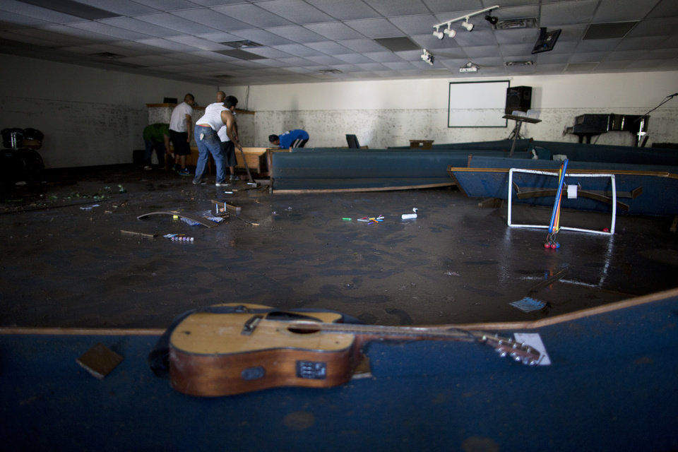 Photo - Volunteers clean up the First Independent Baptist Church after heavy rains caused water levels to rise over four feet in the church before receding on Thursday Oct. 31, 2013 in Austin, Texas. The National Weather Service said more than a foot of rain fell in Central Texas. (AP Photo/ Tamir Kalifa)
