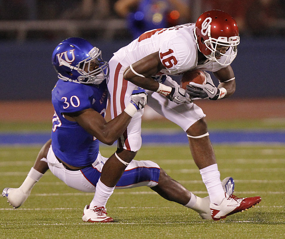 Kansas\' Anthony Davis (30) tries to stop Oklahoma\'s Jaz Reynolds (16) during the college football game between the University of Oklahoma Sooners (OU) and the University of Kansas Jayhawks (KU) on Saturday, Oct. 15, 2011. in Lawrence, Kan. Photo by Chris Landsberger, The Oklahoman