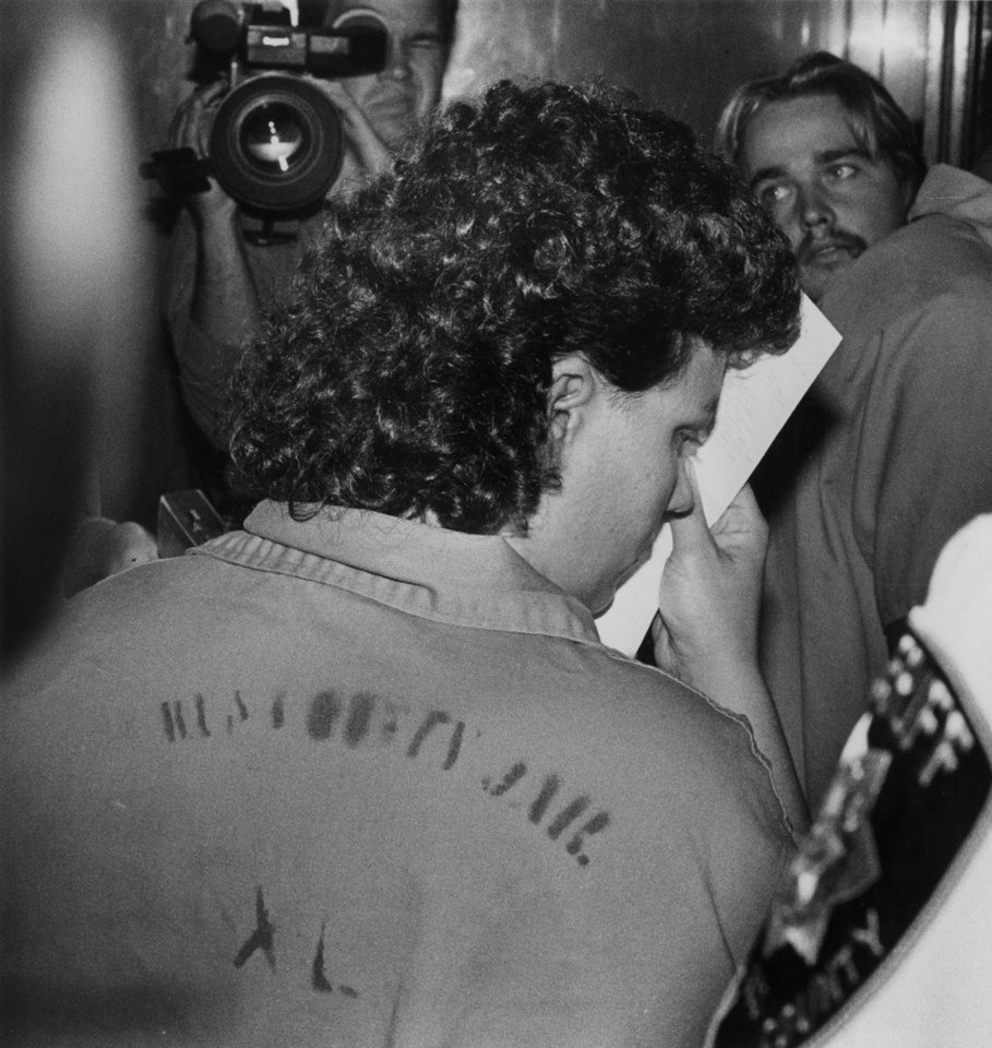 """Marilyn Kay Plantz shields her face from cameras."" Marilyn Kay Plantz, as she is escorted in the courthouse. Staff photo by Paul B. Southerland. Photo taken 9/2/1988 and published in The Oklahoman on 9/3/1988."