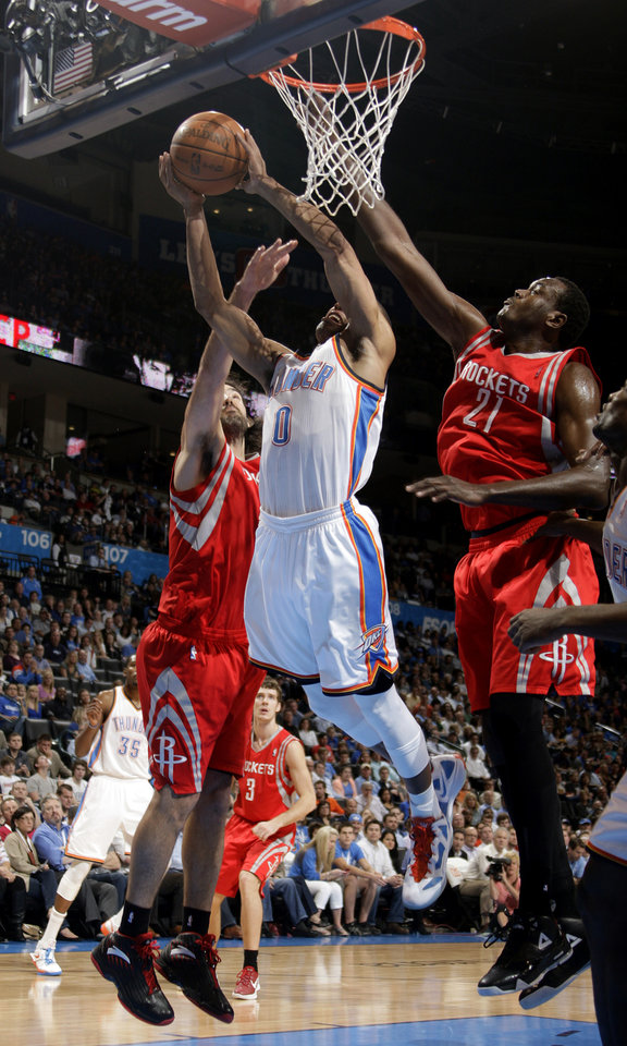 Oklahoma City's Russell Westbrook (0) shoots as Houston's Luis Scola (4) and Samuel Dalembert (21) defend during the NBA basketball game between the Oklahoma City Thunder and the Houston Rockets at the Chesapeake Energy Arena, Tuesday, March 13, 2012. Photo by Sarah Phipps, The Oklahoman.